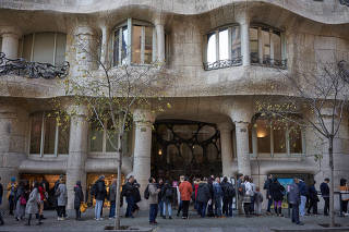 Tourists line up at the gate of the famous building of La Pedrera, designed by Catalan architect Antoni Gaudi, in Barcelona, Spain.