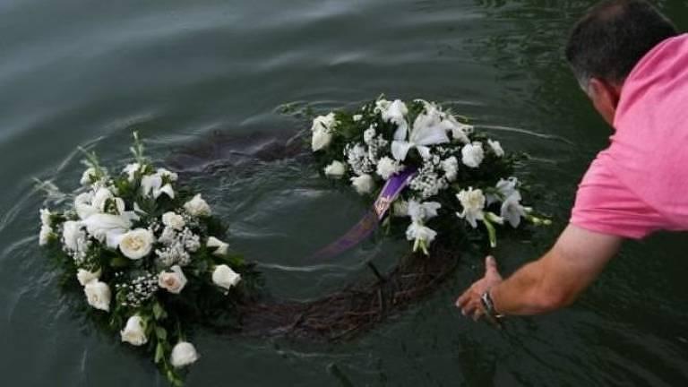 Homem joga coroa de flores em rio
