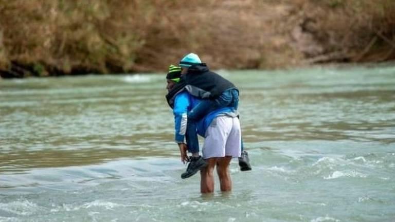 Homem e criança atravessam rio