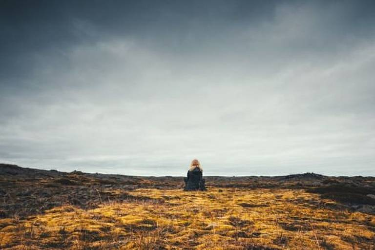 pessoa fotografada ao fundo da foto sentada me meio a um campo com vegetação rasteira amarelada.