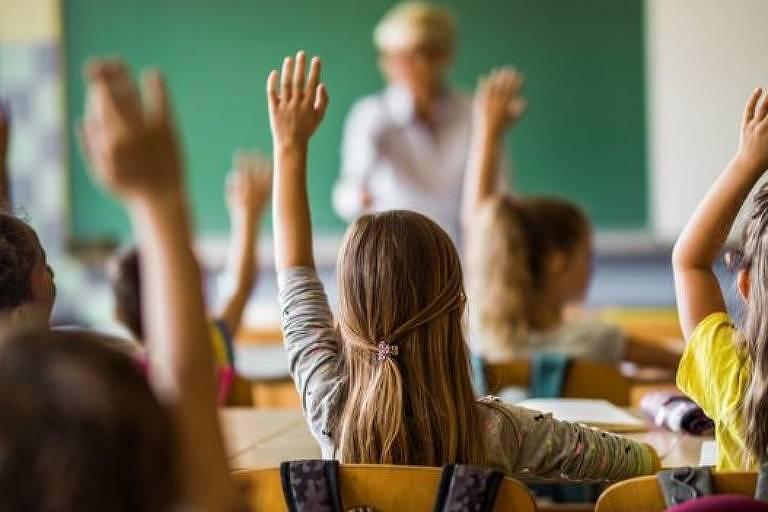 em primeiro plano, crianças fotografadas de costas levantam uma das mãos. Em segundo plano, é possível perceber a lousa e uma pessoa que é o professor ou a professora.