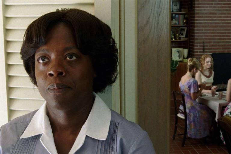 empregada negra de costas para mesa com mulheres brancas