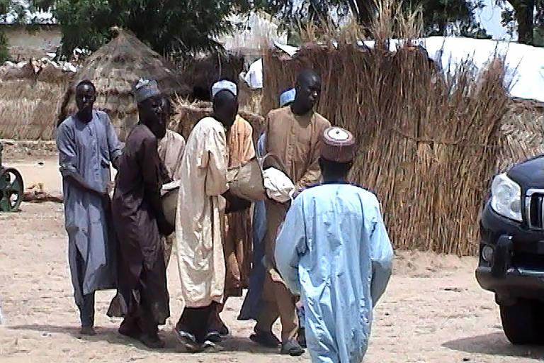 Homens carregam vítima de ataque do Boko Haram em Budu, perto de Maiduguri, na Nigéria