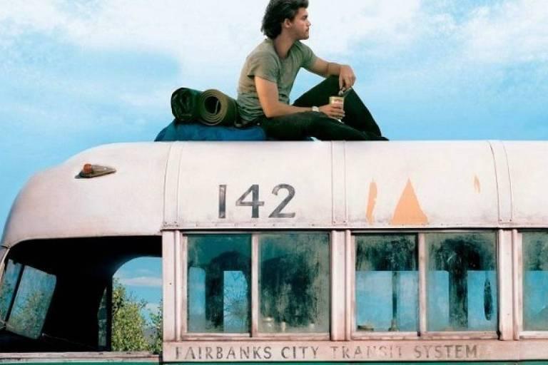 Christopher está sentado en el techo del autobús abandonado, con sus cosas de camping, mirando la vista.