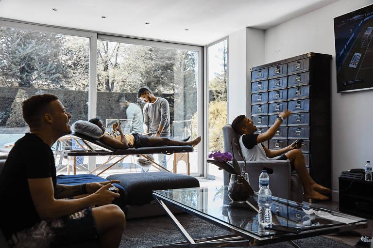 Vinicius Junior, na maca, recebe massagem enquanto seus amigos jogam videogame em sua casa de Madri
