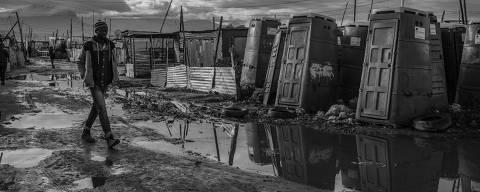 CIDADE DO CABO, ÁFRICA DO SUL, 03.07.2019 - Morador passa em frente a banheiros públicos da Khayelitsha, a maior township (favela) da Cidade do Cabo, e uma das maiores da África do Sul. Não existe rede de água e nem de esgoto na favela e as casas não tem banheiro. (Foto: Lalo de Almeida/Folhapress)