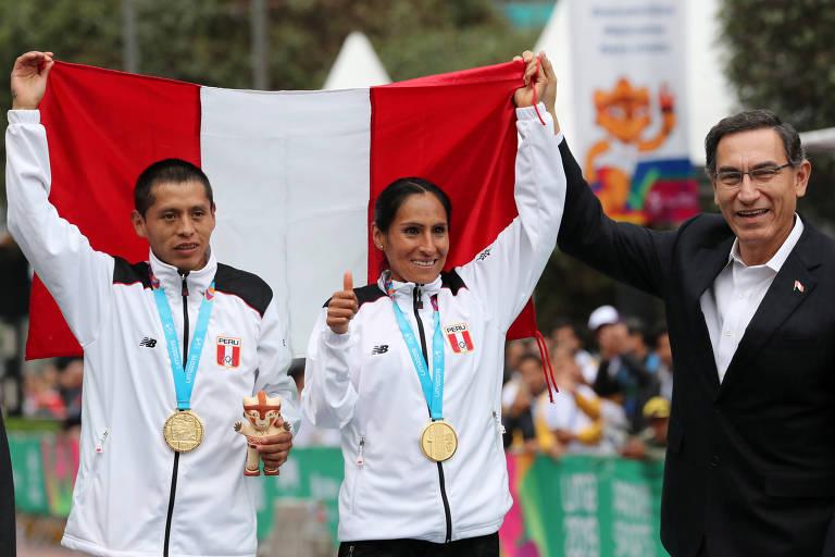 Os peruanos Christian Pacheco (esq) e Gladys Tejeda, após ambos conquistarem o redorde pan-americano da maratona e o ouro na prova