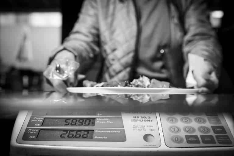Cliente põe prato em balança em restaurante no centro paulistano