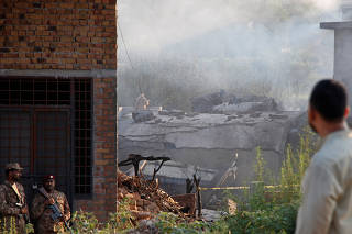 Pakistani soldiers stand guard near a damaged roof after a military aircraft on a training flight crashed in a built-up area in the garrison city of Rawalpindi,
