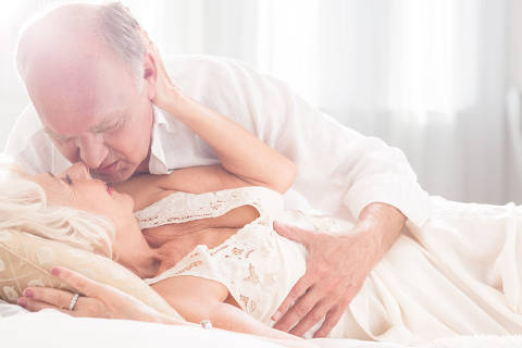Senior man embracing his mature partner, lying in bed, light interior