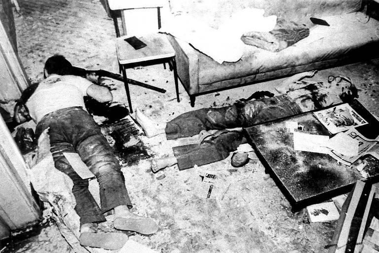 Na imagem em preto e branco, dois corpos aparecem no chão. Um deles, à esquerda, de barriga para baixo e o outro, à direita, de barriga pra cima. Ao lado deles, no ambiente, há um sofá, uma cadeira e uma mesa pequena. Perto de um dos corpos há uma arma.