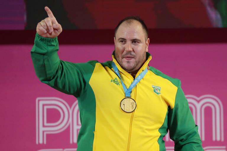 Atleta posa com medalha de ouro. Usa uniforme da seleção brasileira, de cor amarela com detalhes verdes. Com o braço direito, aponta para a frente com o dedo indicador.