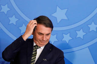 Brazil's President Jair Bolsonaro gestures during a review and modernization ceremony of occupational health and safety work at the Planalto Palace in Brasilia