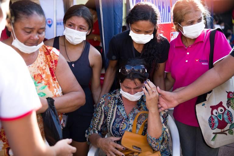 Mulheres em pé e sentadas usam máscaram brancas