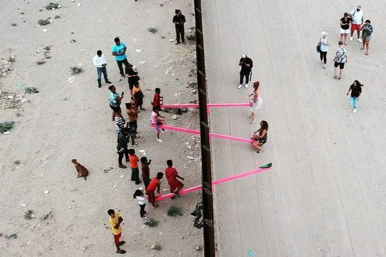 Crianças do México e dos EUA brincam com gangorra instalada no muro da fronteira