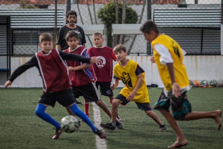 João Marcos, ao fundo, observa seus alunos durante o treinamento coletivo na escolinha de futebol