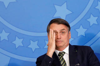 Brazil's President Jair Bolsonaro reacts during a review and modernization ceremony of occupational health and safety work at the Planalto Palace in Brasilia