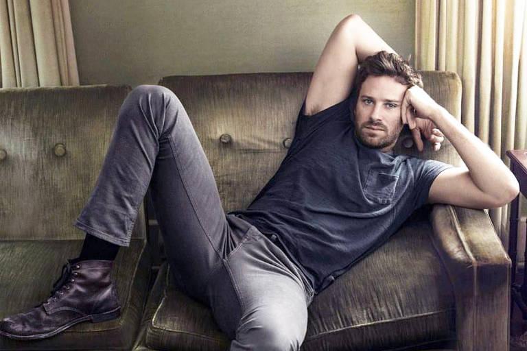 Armie Hammer sentado no sofá vestindo camiseta preta e uma calça jeans cinza.