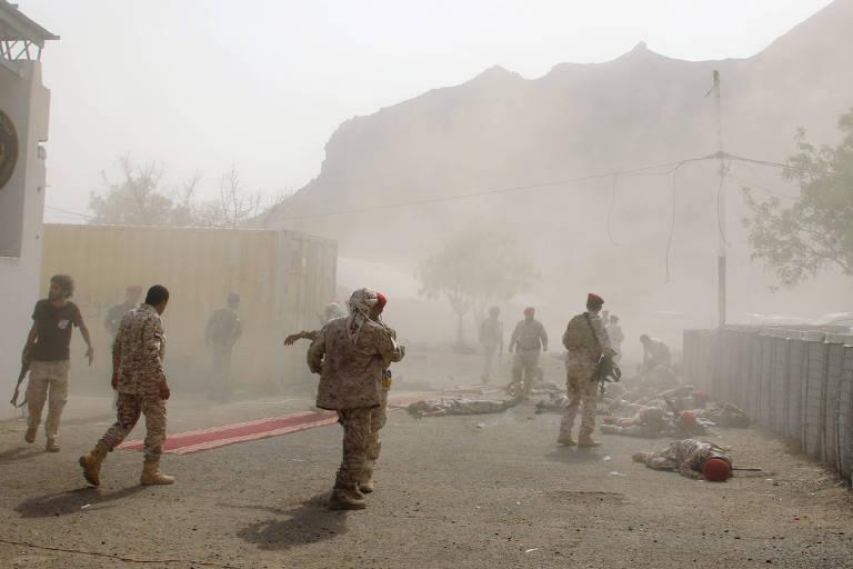 Membros de forças de segurança caídos no chão após ataque com míssil em Aden, no Iemên
