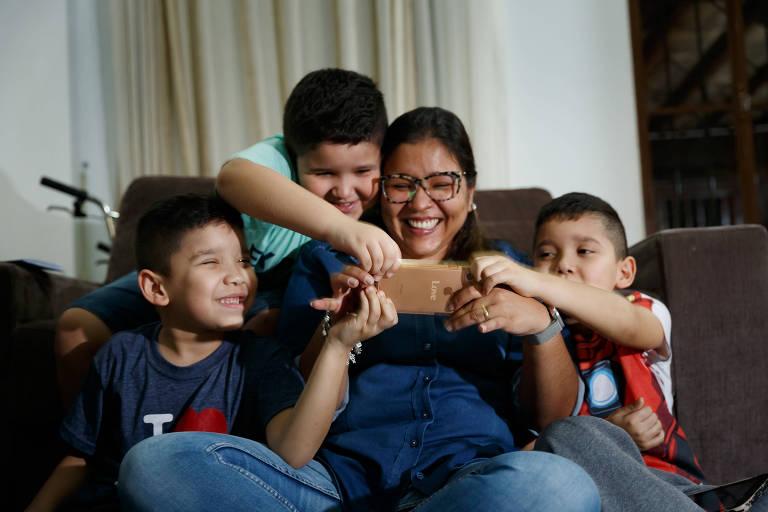 A dona de casa Carla Daniela de Freitas Giamundo, 32, com os filhos Pedro (camiseta azul), Lucas (verde) e Rafael (homem de ferro)
