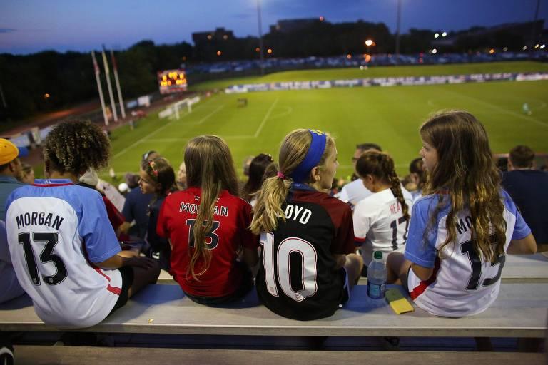 Com camisas da seleção, jovens assistem a um jogo da liga feminina de futebol dos Estados Unidos