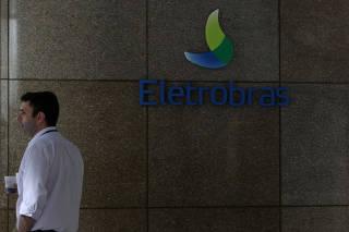 A person stands next to the logo of Brazil's power company Eletrobras in Rio de Janeiro