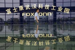 File photo of a man walking past a logo of a Foxconn factory in Wuhan