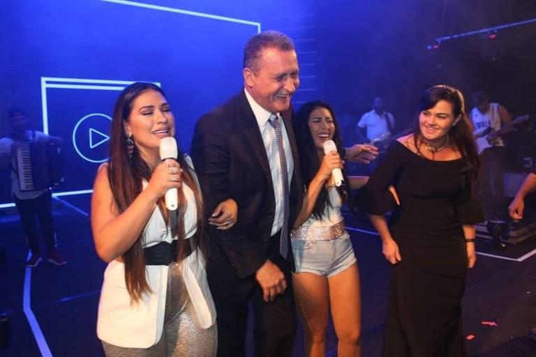 O governador da Bahia, Rui Costa, está entre as cantoras Simone e Simaria. Ele veste terno e as cantoras estão com microfones nas mãos.