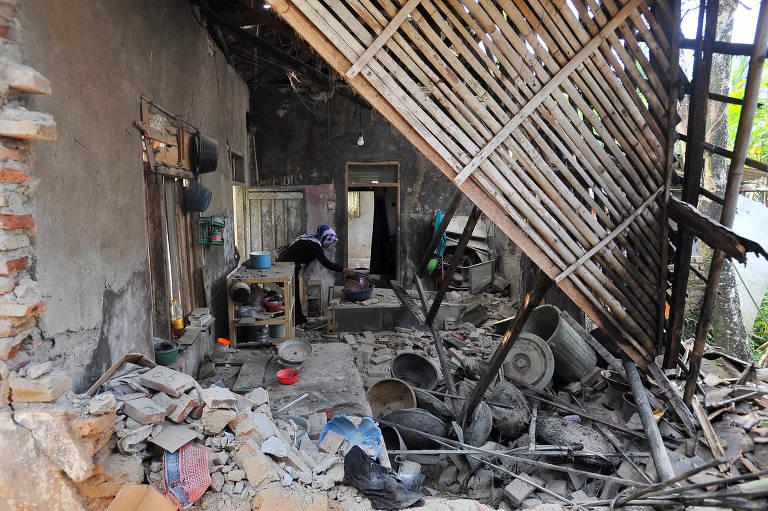 Mulher busca pertences no que restou de sua casa, destruída pelo terremoto de magnitude 6,9, em Pandeglang, na província de Banten, na Indonésia