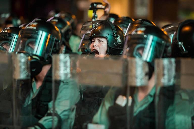 Policiais alertam manifestantes no distrito de Mong Kok, em Hong Kong