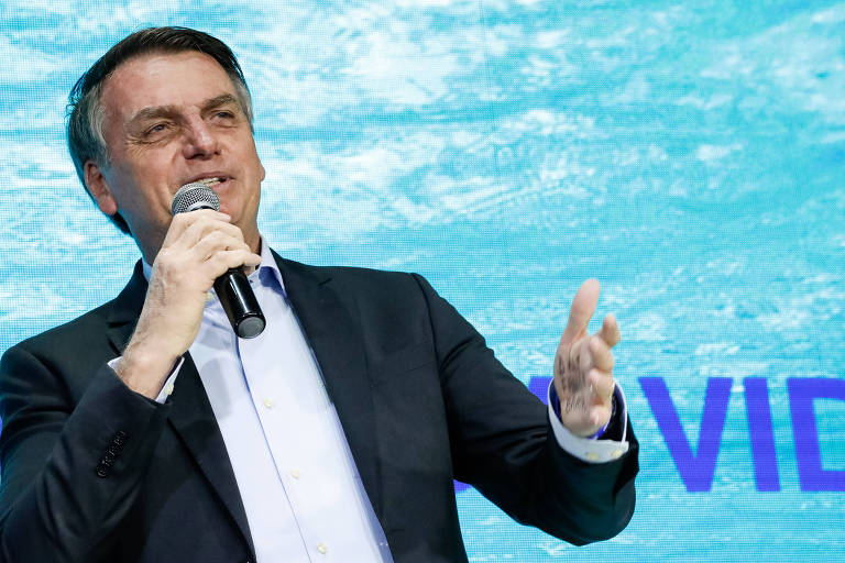 """Presidente Jair Bolsonaro, do lado esquedo da foto, fala ao microfone vestindo camisa e paletó. Ele aparece apenas da cintura para cima. Com a mão esquerda, gesticula. O fundo da foto é azul e é possível ver parte do nome da Igreja escrito: """"vida"""""""