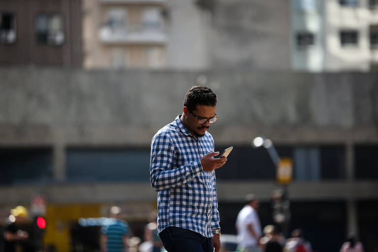 Paulistanos usam celular na região central de SP; cerca de um terço dos registros eletrônicos de roubos e furtos desses aparelhos é rejeitado