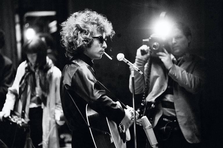 Homem branco com cabelo curto toca violão e fuma cigarro em frente a microfone enquanto está em cima de um palco. Foto em preto e branco