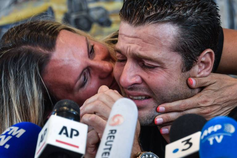 Franky Zapata chora e é confortado por sua mulher, Krystel, durante entrevista coletiva em Sangatte