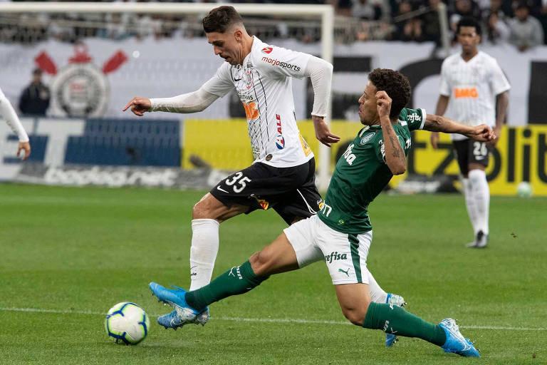 O lateral esquerdo corintiano Danilo Avelar tenta escapar da marcação do lateral direito palmeirense Marcos Rocha.