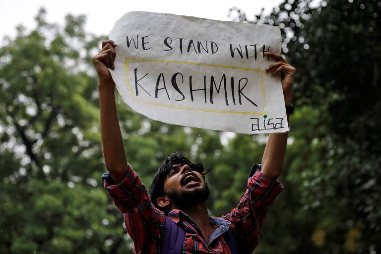 """Manifestante em Nova Déli com cartaz que diz """"nós estamos com a Caxemira"""", em protesto contra decisão do governo indiano de retirar status especial da região"""