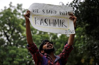 A man holds a sign and shouts slogans during a protest after the government scrapped the special status for Kashmir, in New Delhi