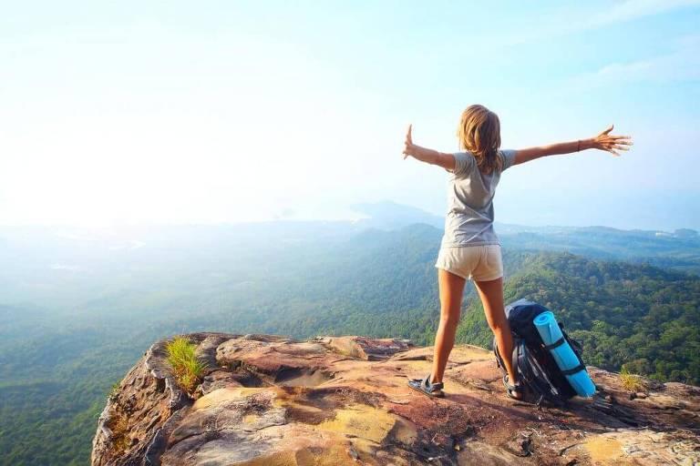 mulher de braços abertos em uma montanha