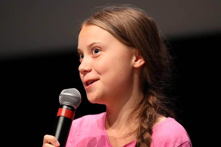 Menina segura microfone enquanto fala