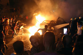People extinguish a fire from a blast outside the National Cancer Institute, Cairo