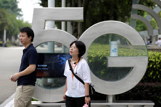 FILE PHOTO: Employees wait for a shuttle bus at a 5G testing park at Huawei's headquarters in Shenzhen