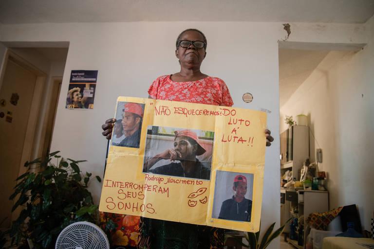 """Mulher posa em pé, em uma sala de estar, com cartaz em que estão fotos de um jovem negro de boné sob os dizeres """"interromperam seus sonhos"""""""