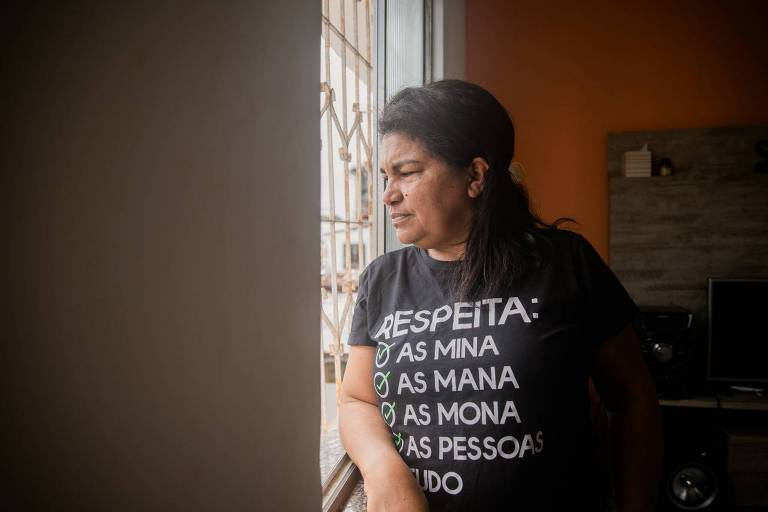 """Mulher de meia idade com camiseta preta onde se lê """"Respeita As Mina, As Mana, As Mona, As Pessoas"""" observa por uma janela"""