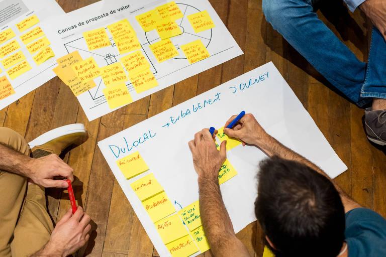 alunos do programa de aceleração da Artemisia preenchem papéis e cartazes com ideias e estratégias de impacto social