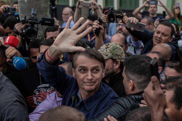 Jair Bolsonaro cercado por seguranças, após votar no primeiro turno da eleição, no Rio