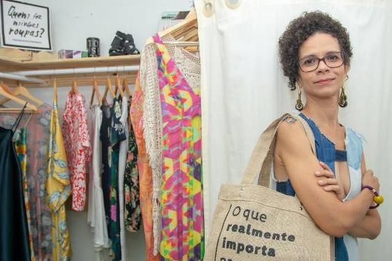 Ana Fernanda, criadora do Justa Moda, é negra de pele clara e usa óculos. Está com os braços cruzados dentro de uma loja de roupas de consumo sustentável