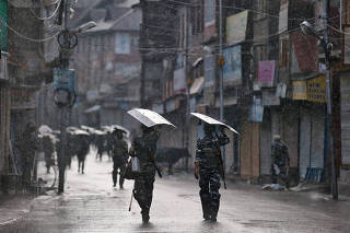 Indian security forces personnel patrol a deserted street during restrictions after the government scrapped special status for Kashmir, as it rains in Srinagar