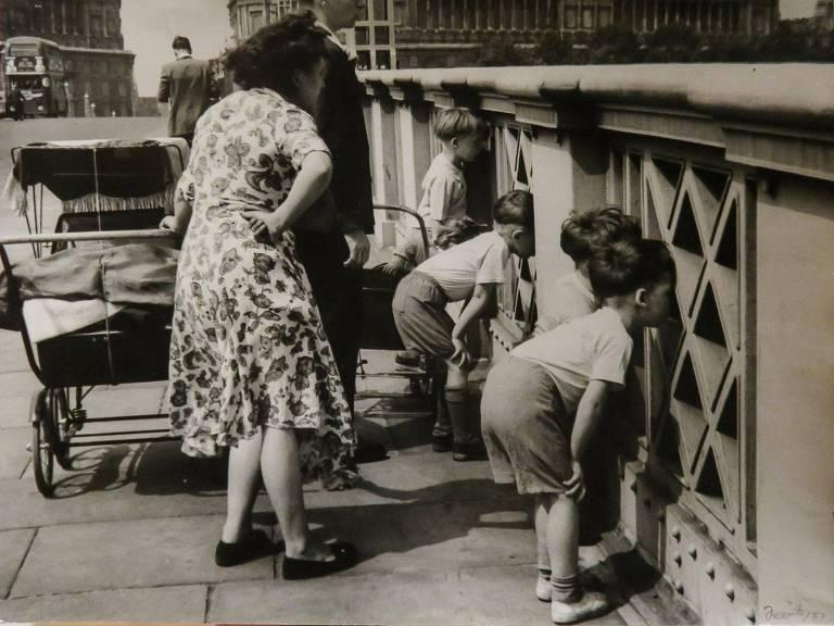 crianças olham por vão de ponte