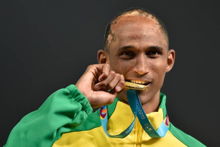 Homem morde medalha dourada