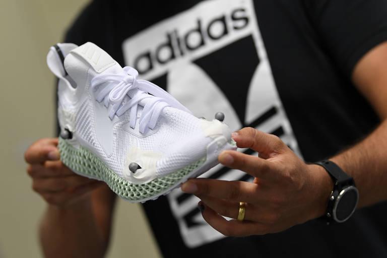 Homem com a camiseta da Adidas segura um tênis para a foto